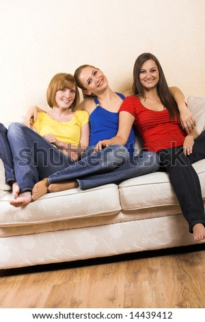 Three young beautiful women are sitting on their lounge