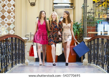 Three Young beautiful women with some shopping bags walking in the mall