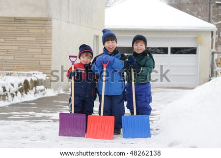 Three young boys take pride in completing a big shoveling job - stock photo