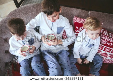 three young brothers in identical pajamas holding mugs of milk sitting on a sofa in the dining room - stock photo
