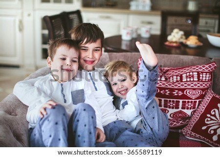 three young brothers in identical pajamas sitting on a sofa in the dining room - stock photo