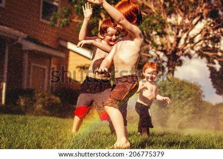 Three young brothers playing in the sprinklers on a hot day -- image taken outdoors in Reno, Nevada, USA - stock photo