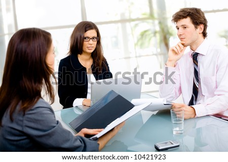 Three young businespeople working in team at office, smiling.