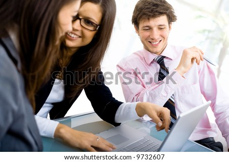 Three young businespeople working in team at office, smiling. - stock photo