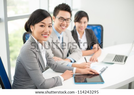 Three young business colleagues sitting in office during meeting - stock photo