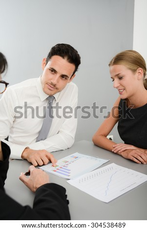 three young business people at business meeting looking and discussing data documents in office