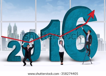 Three young business people lifting upward arrow in the office with numbers 2016 - stock photo