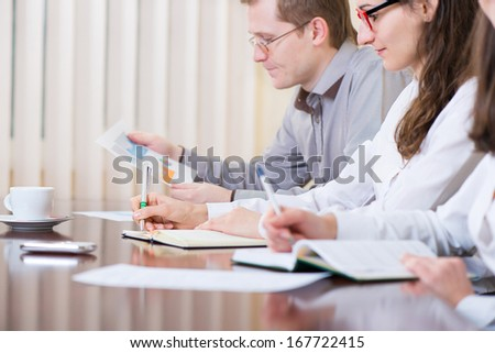 Three young business people sitting at seminar, primary focus on hand - stock photo