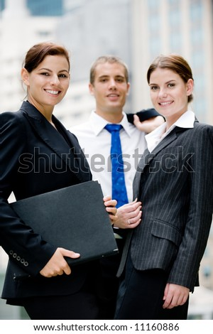 Three young business people standing together outside - stock photo