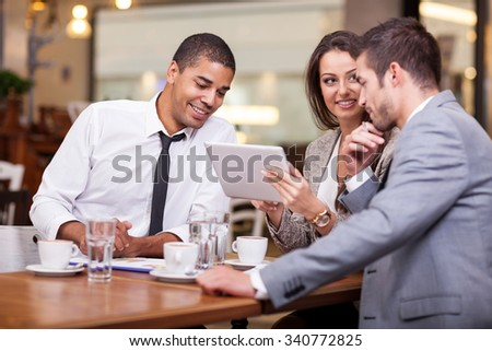 Three young businessman on a break at the restaurant, discuss new ideas and projects - stock photo