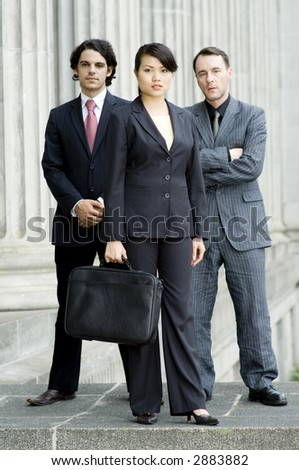 Three young businessmen and women standing in front of an old building