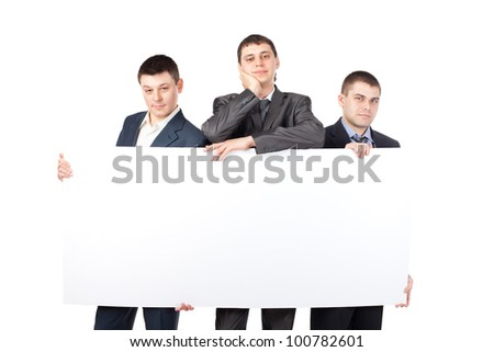 Three young businessmen hold up a large blank sign isolated on white background - stock photo