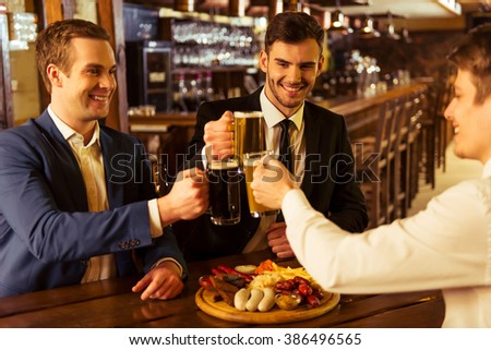 Three young businessmen in suits are smiling and clanging glasses of beer together while sitting in pub - stock photo