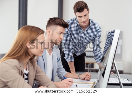 Three Young Businessmen Sitting at the Table and Looking at the Computer Screen Together with Serious Facial Expressions