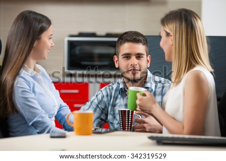 Three young businesspeople having a coffee break in an office - stock photo