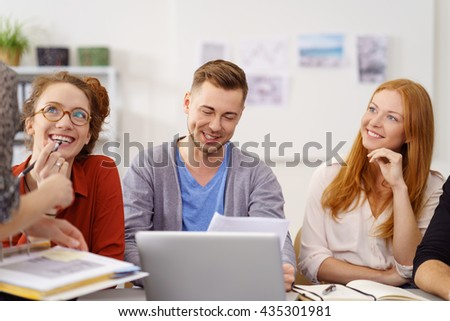 Three young businesspeople in a meeting sitting listening to a team leader or manageress perched off to the side on the table with pleased smiles - stock photo