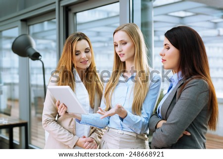 Three young businesswomen discussing ideas at office - stock photo