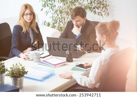 Three young busy businesspeople at work - stock photo