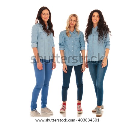 three young casual women in jeans clothes standing together on white background