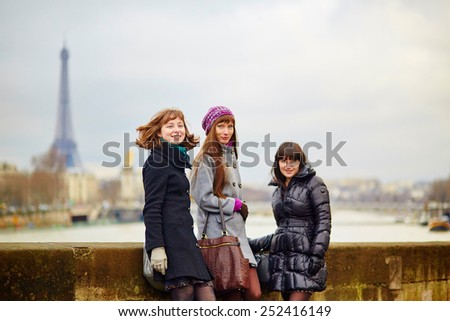Three young cheerful girls walking together in Paris - stock photo