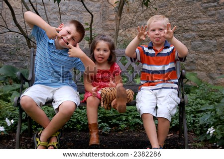 Three young children sitting on a bench making silly faces. Could be spring or summer. - stock photo