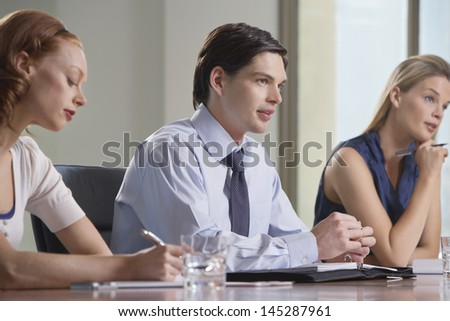 Three young colleagues sitting at a business meeting