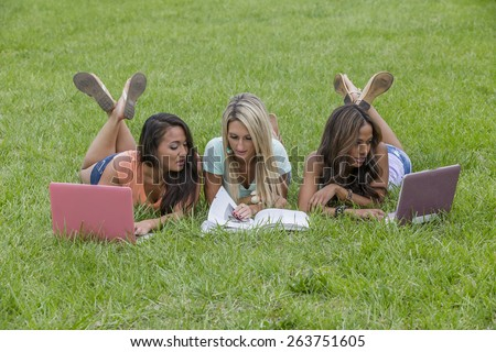 Three young college coeds studying in a park - stock photo