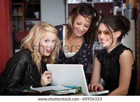 Three young college students laughing while looking at computer in a coffee house - stock photo