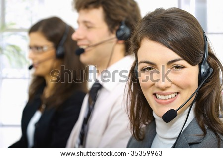 Three young customer service operators sitting in a row and talking on headset. Selective focus on women in front. - stock photo