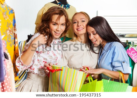 Three young excited women with shopping bags