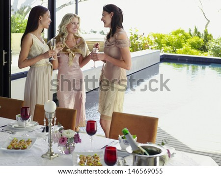 Three young female friends with champagne flutes at dinner party - stock photo