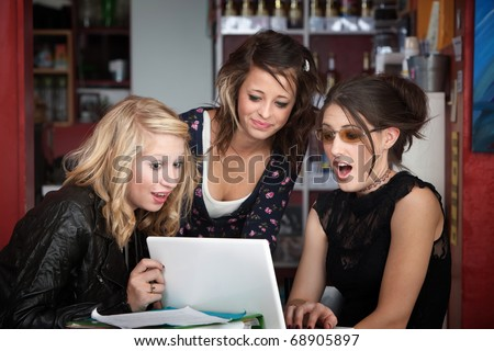 Three young female students surprised while looking at a computer - stock photo