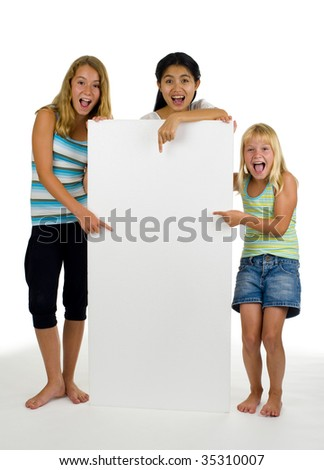 three young females point at something on a white board - stock photo