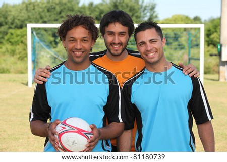 Three young footballers in front of goal