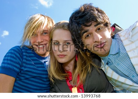 Three young friends embrace over sky background - stock photo