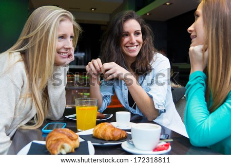 three young friends having breakfast on a morning shopping in the city - stock photo