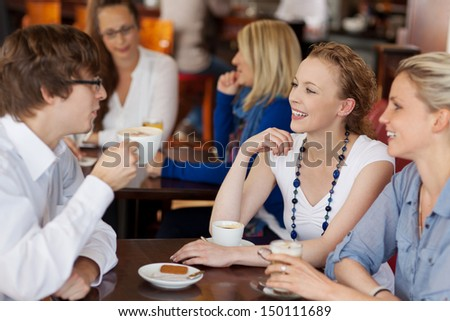 Three young friends having coffee together in a cafe seated around a small table chatting and smiling - stock photo