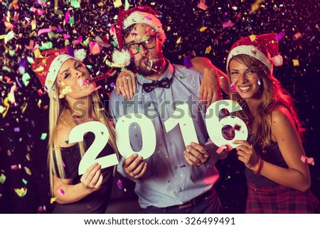 Three young friends having fun at New Year's Eve Party, holding cardboard numbers 2016 - stock photo