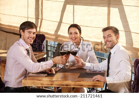 Three young friends having wine together in cafe. two man and woman sitting around table chatting and smiling  - stock photo