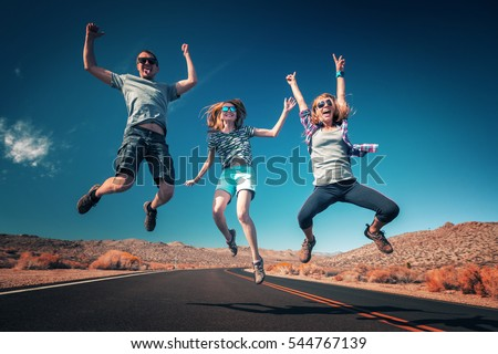 Three young friends jumping and having fun on the empty asphalt road