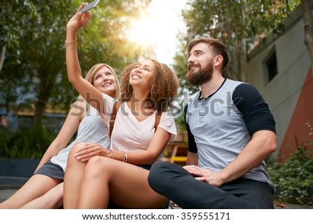 Three young friends taking a selfie with cellphone. Multiracial group of young people having fun together while sitting outdoors. - stock photo