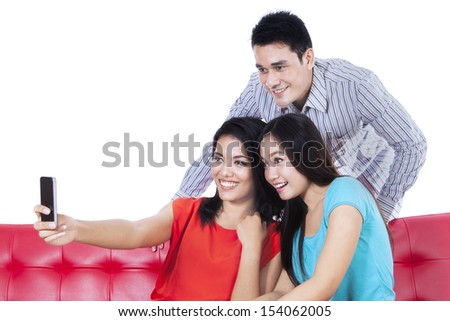 Three young friends taking photo by mobile phone on white background - stock photo
