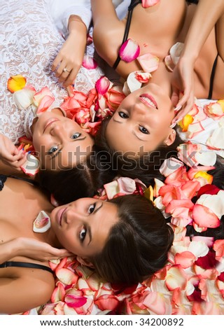 Three young girl and petals of roses