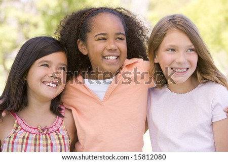 Three young girl friends outdoors smiling - stock photo