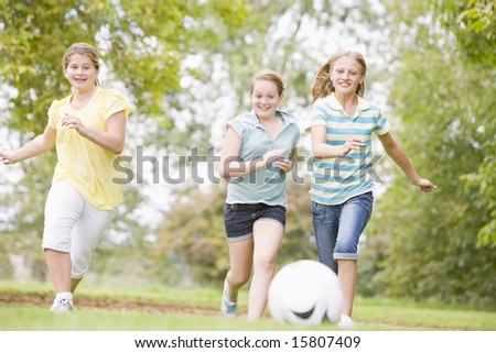 Three young girl friends playing soccer - stock photo