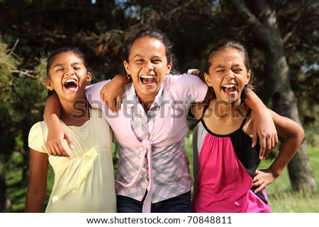 Three young girl friends share hilarious moment of laughter