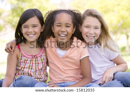 Three young girl friends sitting outdoors smiling - stock photo
