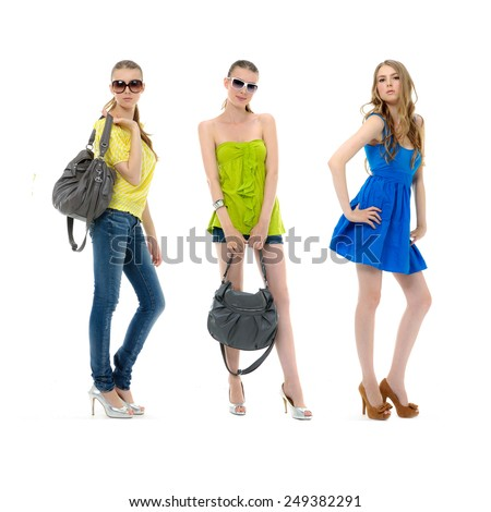 three young girl in summer dress in sunglasses and with bag posing - stock photo