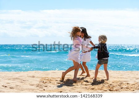 Three young girlfriends playing game on beach. - stock photo