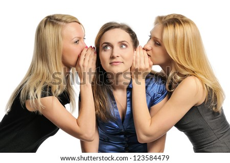 Three young girls gossiping, whispering to each other's ears. Isolated on white. - stock photo